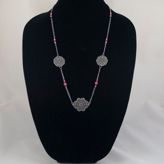 Three Gunmetal Floral Filigree Pendants with Red Bead Accents on a Gunmetal…