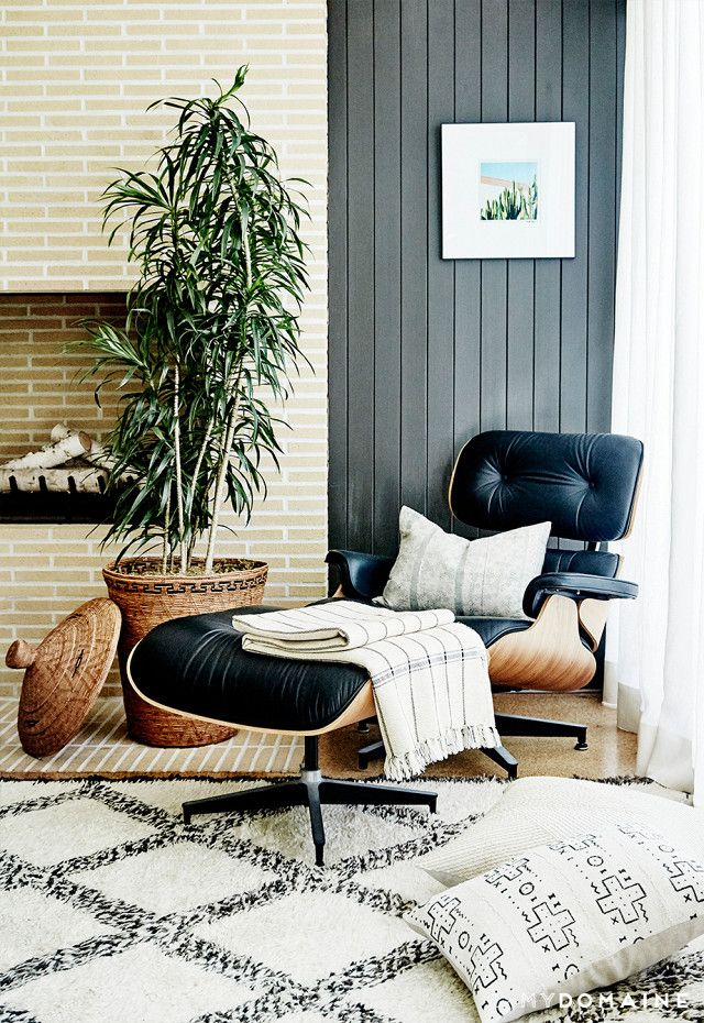Cozy living space with a fireplace, a large plant, a Eames lounge chair, and gray shiplap walls