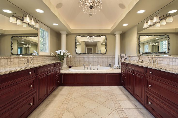 Perfectly symmetrical bathroom featuring cherry wood cabinets, granite countertop, twin columns surrounding bathtub and mirrors all around.