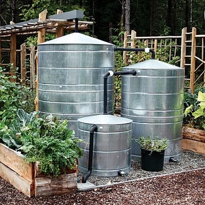 """Did you know that 1"""" of rain water puts about 600 gallons of water atop a 1,000 square foot house? Captured directly from a downspout or rain chain, a cistern will have your garden water ready. These cisterns collect rainwater from a nearby roof using rain gutters, and when the tanks are full water is dispersed through a gravity fed drip system that irrigates crops. Also can be filtered and used for bathing, washing clothes, dishes, etc."""