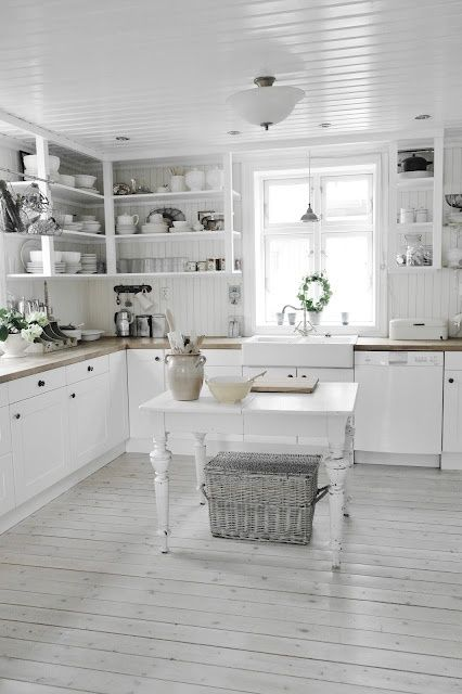 White washed and wonderful!  Simple cabinets...open shelf storage...wooden planked floors and ceilings and concrete counter tops along with a vintage farmhouse table and a touch of wicker give this kitchen a natural and beautiful glow. Nothing fancy but so much heart.