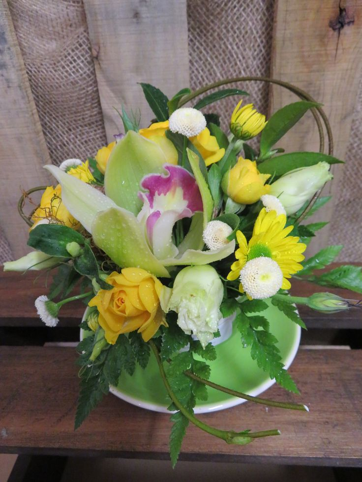 Sweet teacup arrangement made with spray rose and orchids. Lovely keepsake. Created at Florist ilene