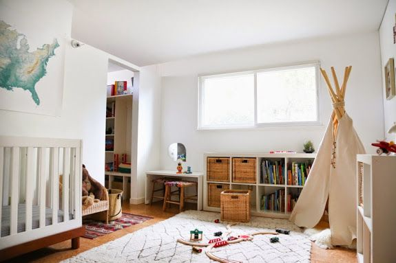 Lovely earthy nursery with a tepee, expedit storage, and the sweetest little mini parsons desk with woven stools