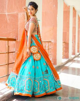 Sangeet Lehengas - Orange and Turquoise Lehenga | WedMeGood | Orange Thread Work Blouse and Turquoise Flared and Pleated Lehenga with Orange Mirror Work, Orange Dupatta and Orange Big Latkans | #wedmegood #sangeet #lehengas #turquoise