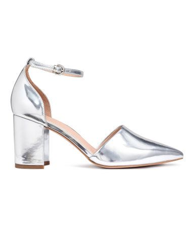 Silver-colored. Open-sided pumps with pointed toes, covered block heels, and an adjustable ankle strap with a metal buckle. Imitation leather lining and