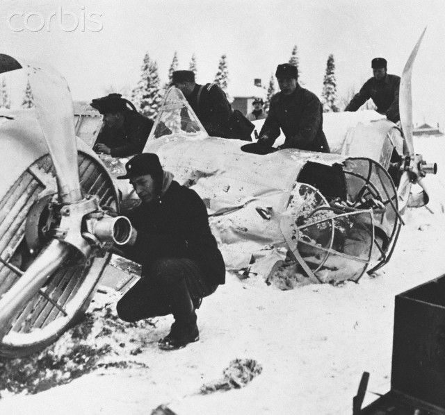Finnish anti-aircraft crew inspect the wreckage of a twin-engine Soviet bomber brought to earth in one of Soviet raids on Finland. December 28, 1939