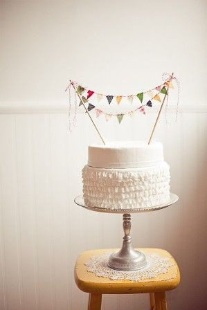 simple white cake with bunting for gender reveal?? Love it!