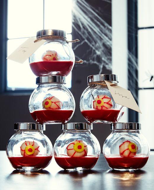 Petits bocaux en verre empilés, remplis de gélatine rouge et de bonbons en forme d'yeux !