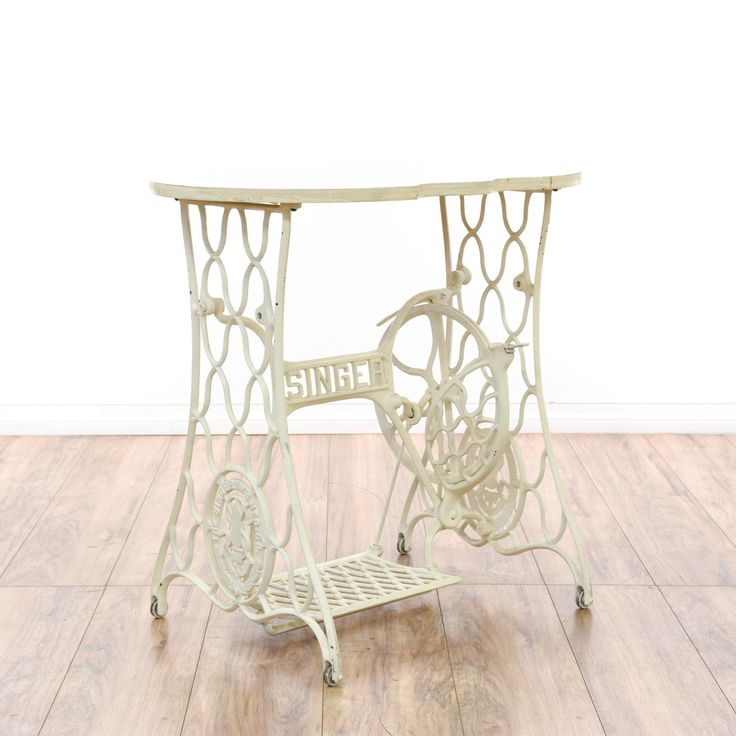 """This """"Singer"""" sewing table is featured in a wrought iron metal with a white painted finish. This tall side table has a curved top with an old sewing machine base and ornate latticework accents. Cottage chic table perfect for decorating a room! #cottagechic #tables #endtable #sandiegovintage #vintagefurniture"""