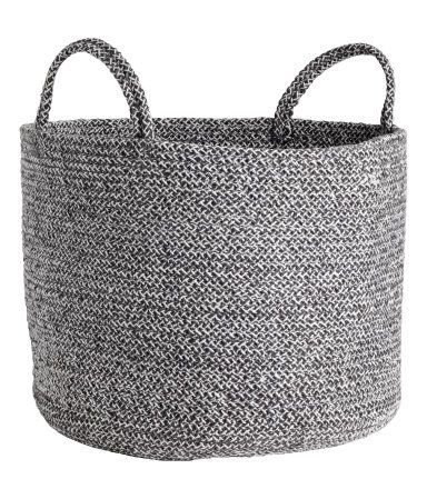 Dark gray melange. Storage basket in thick jute with two handles at top. Height 11 in., diameter 13 3/4 in.