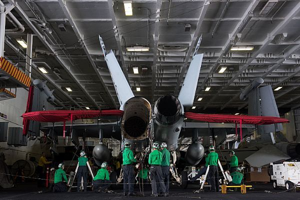 Sailors jack up an EA-18G Growler assigned to the Wizards of Electronic Attack Squadron (VAQ) 133 in USS John C. Stennis (CVN 74) hangar bay for routine maintenance checks.