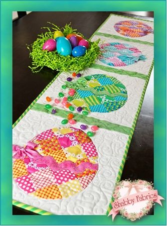 """Patchwork Easter Egg Table Runner Pattern: Add some sparkle to your Easter table with this darling Easter Egg Runner! This pattern shows you to make this quick and easy project featuring patchwork eggs and glitter accents. Finished size is12 1/2"""" x 53"""". Designed by Jennifer Bosworth of Shabby Fabrics."""