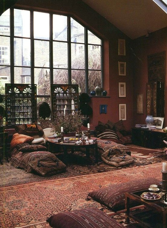 Urban bohemian loft. I like how the weathered fabrics and furnishings contrast with the city view.