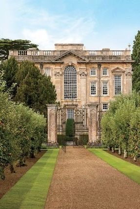 Rows of apple trees lead to the  entrance of Easton Neston, Northamptonshire,  the 1702 masterpiece by Nicholas Hawksmoor (1661-1736), an ingenious, inventive architect who also had a hand in Blenheim Palace and Castle Howard. From its stone lions marching along the roofline to its wildly attenuated windows, the ashlar building represents the domestic high point of the English Baroque, a flamboyant style that flowered briefly before Palladian stateliness became prominent.