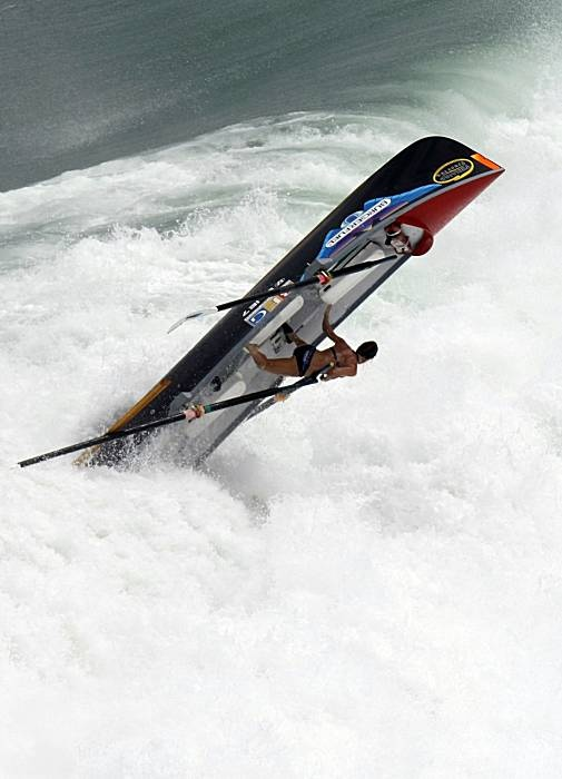 A crashing wave pitches a rower from her surf boat during ...