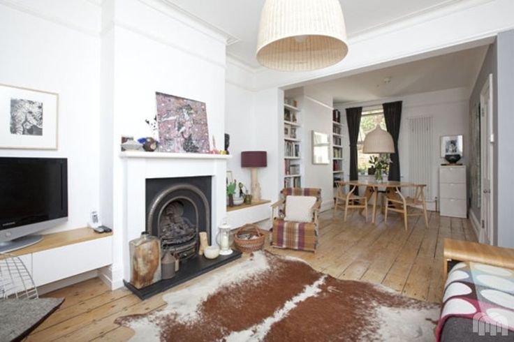 through lounge, exposed floorboards, white walls, low shelf for tv
