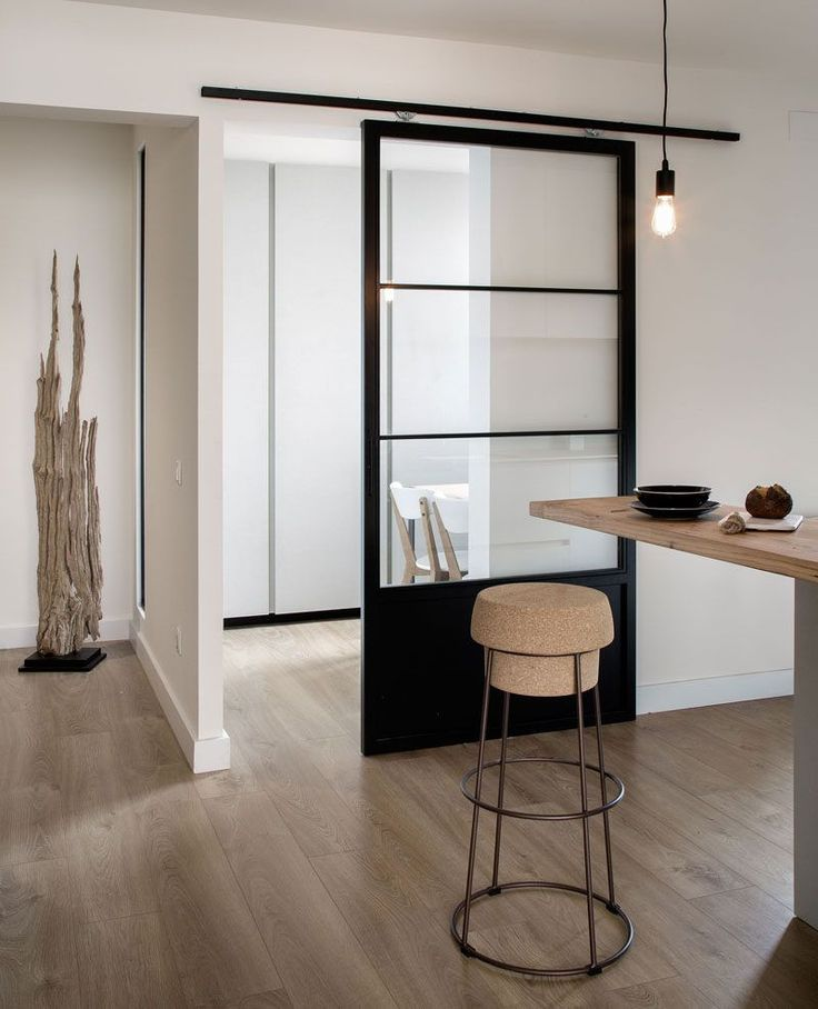 This glass and black sliding door separates the main part of the kitchen from a dining area and gives the space a modern industrial look that's accentuated by the exposed hanging bulb and metal bar stool.