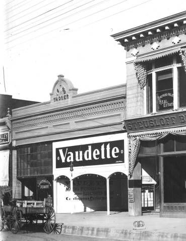 Vaudette Theater on Court Street in Salem, Oregon, 1906 :: Ben Maxwell Collection Pictured is the Vaudette Theater, an early Salem movie house, that was housed in the Wagner Building. In the same building was the Capital City Creamery. It was located on Court Street across from Miller's Store. The front of the theater is painted white and the building appears to be one story. A real estate office is on the right. A horse drawn wagon is in front of the theater and an early hitching post is on…