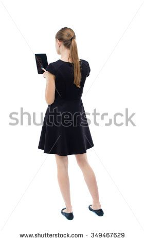 back view of standing young beautiful  girl with tablet computer in the hands of. girl  watching. Isolated over white background. blonde in a black dress presses a finger on screen of your smartphone