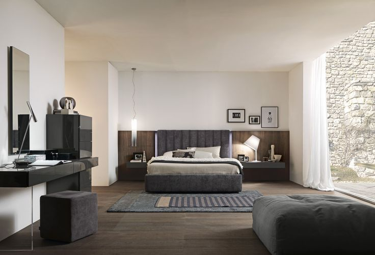"Dado tube h.1195 bed upholstered with mistral fabric. Dado wall panelling in ""aged"" tabacco oak, optional side led lighting. Hung Wing night stands in matt grigio antracite lacquer.__ Letto Dado tube h.1195 imbottito in tessuto mistral. Boiserie Dado in rovere ""vissuto"" tabacco, illuminazione a led laterale optional. Comodini sospesi Wing laccato lucido grigio antracite."