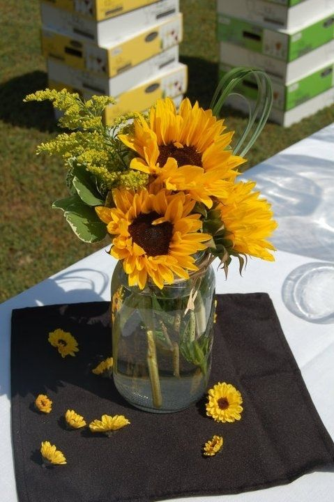 Rustic fall centerpieces made from sunflowers, solidago, pit and bear grasses in a mason jar with viking mum heads scattered about the table