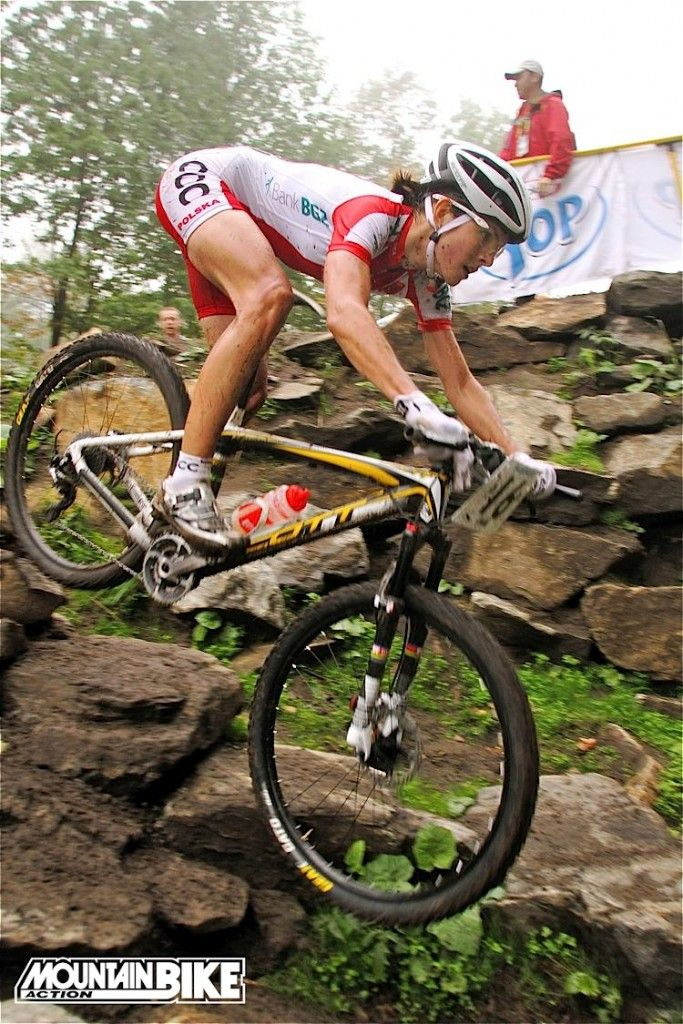 Maja Wlosczsowska (pronounced: MY-a VWOESH-tof-ska) blasts down a steep slope in the rain in Mont-Sainte-Anne, Quebec, on her way to winning the UCI Elite Women's Cross-Country World Championship for 2010. If she weren't an athlete, she told us, she'd be a mathematician. She has a Masters degree in mathematical finance and taught at the university level in her native Poland while working towards her degree. She also has an Olympic silver medal in her collection. Photo: JK/Mountain Bike…