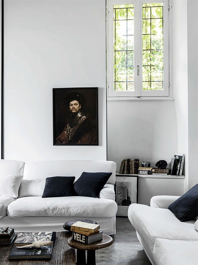 This dark, Rembrandt-y painting - which you might think would not work int his room - really looks great against all the white (and married with the dark throw pillows).