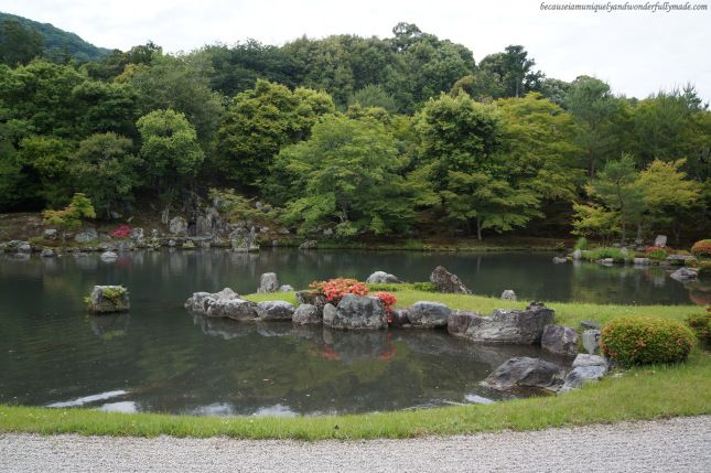 The garden featuring Sogen-chi pond (曹源地) surrounded by rocks, pine trees, maple trees and mountains at Tenryu-ji Temple (天龍寺) in Arashiyama district in Kyoto, Japan.