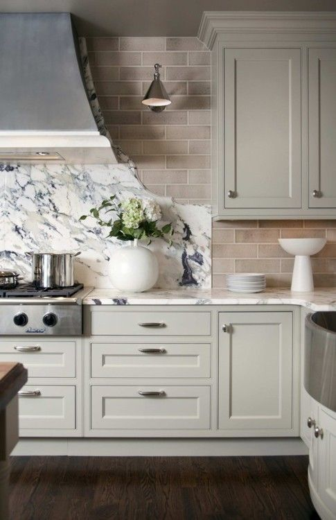 Green-gray cabinets, pink-beige bricks, blue/green-gray marble