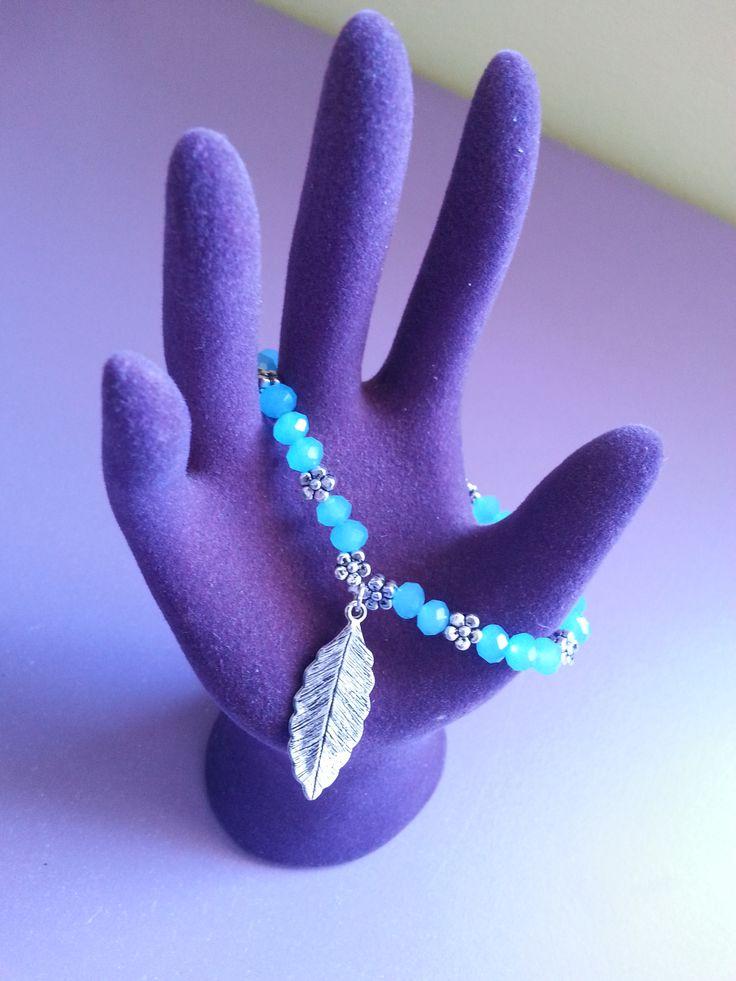 Pulsera de piedras azul celeste con pequeños remaches entre ellas y una bonita hoja de plata. Perfecta para cualquier ocasión.