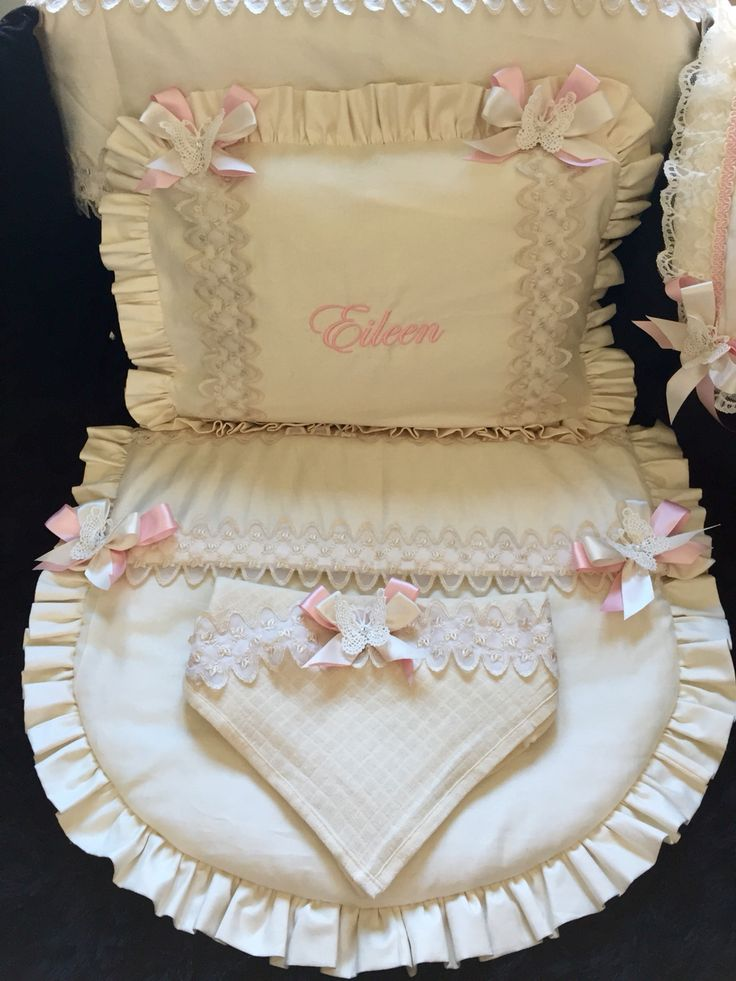 Cream with shear rose bud lace pram set. Personalised in baby pink with double Swarovski matching bows with lace butterfly's. Matching sheet and muslin. Andrade to order pram quilt