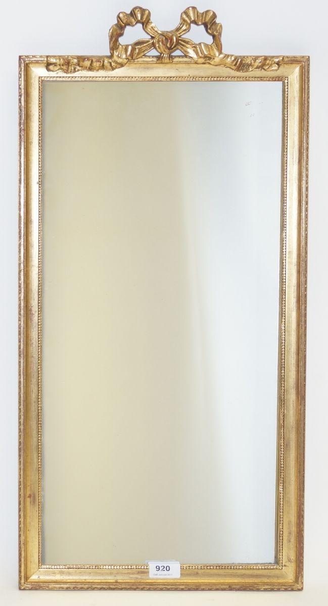 Een rechthoekige halspiegel in goudkleurige striklijst met parelrand