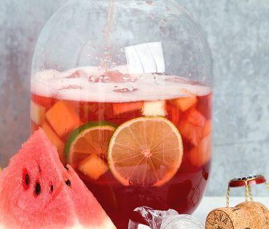 Blanda en frisk vackert rosa alkoholfri bål. Här låter vi tärnad melon i olika färger och lime i skivor marinera i tranbärsdryck. När det väl är drinkdags tillsätts en flaska mousserande rosévin utan alkohol.