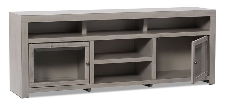 Fall in love with the rustic vibe of this Monterrey TV stand. With five open shelves, this stand offers more than enough space for your PVR, DVD player, video game console and more. Display your movie collection or Hollywood paraphernalia behind the framed, bevelled-glass doors. A semi-matte grey is coated in whitewash to create the gorgeous, distressed finish of the Monterrey collection, while metal hardware is the perfect complement to the light finish. Plus, your 70-inch television will…