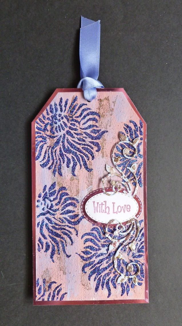 'My Carnation' Tag, - Imagination Craft's-Clover & Baltic blue MDF paints.  Clear embossing powder.  Blue Lagoon Sparkle Medium.  Metal spatula.  Carnation panel stencil.  Magi-bond glue.  Cafe Creme Rusty Patina.  Pink metallic pad.  Gilding glue, gilding flakes.  Pink mirri card.  Oval & Vine dies - Just Rite.  With love stamp from my stash.   April 2017.  Designed by Jennifer Johnston.