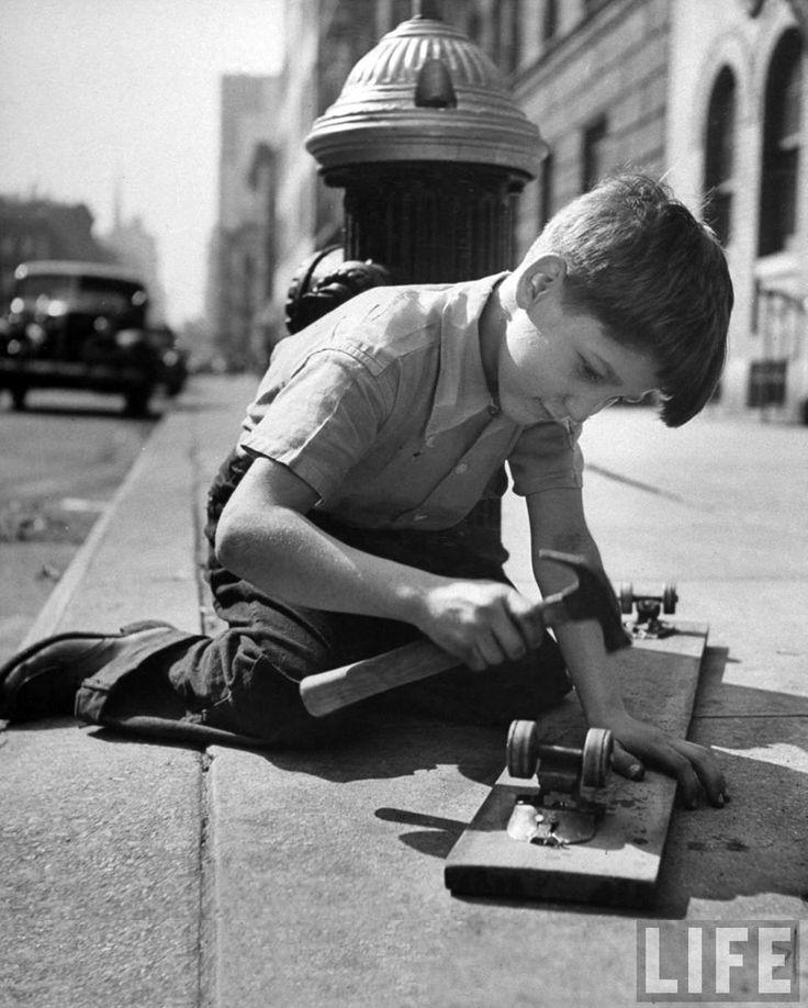 Un chico clavando las piezas de rodadura de unos patines viejos a un tablón de madera como primer paso hacia la fabricación de un monopatín, gracias a unos tablones de madera desechados. Nueva York, junio de 1947