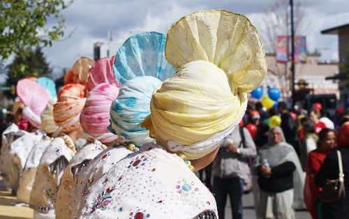 A row of young boys in traditional costumes and colourful hats sit on a stage and watch the festivities at the Vancouver Vaisakhi Parade in April 2015.