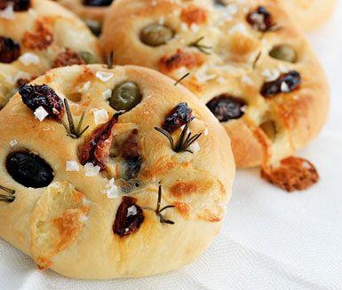 Focaccia med getost och rosmarin är sagolikt gott bröd som du enkelt bakar själv. Tomat, oliv, getost och rosmarin trycks ner i degen innan jäsning och är fenomenala smaksättare.