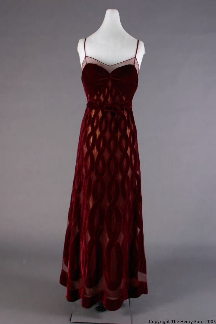 Evening Dress, 1940. Patou, Jean, 1887-1936. Dress of wine-colored velvet with intertwining serpentine cut-out design over wine net; gold/navy blue lame shows through cut-outs. Serpentine figuring is smaller at bustline and larger at hem. Heart-shaped bodice with spaghetti straps and raised waistline. Machine and hand sewn. Clothing label on dress: Jean Patou/PARIS. Front