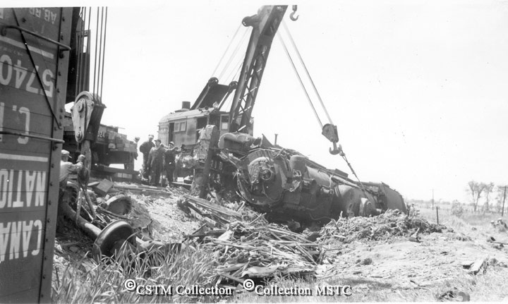 """Location:  Woodlawn, ON  Railway Name:  CANADIAN NATIONAL RAILWAYS  Date:  1951-00-00  Caption:  """"Views of a CNR wreck at Woodlawn, Ontario in 196?, when an eastbound freight hauled by locomotive no. 5291 (4-6-2) ran into the rear end of the mixed train which was on the main line. Wrecker at Woodlawn station."""""""