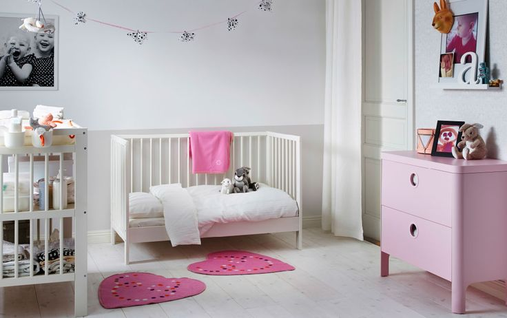 A nursery with a white crib converted into a bed. Shown together with a white changing table and a pink chest of drawers.