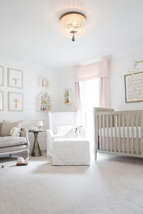 Stunning gray and pink nursery boasts a Wingback Slipcovered Swivel Glider & Ottoman placed catty corner beside a window dressed in Cotton Canvas Drapery Panels in Petal hung next to a Restoration Hardware Baby & Child Marcelle Crib placed on a RH Baby & Child Scallop Wool Rug beneath Antique Sheet Music - Hush Little Baby lit by a Dauphine Pendant.
