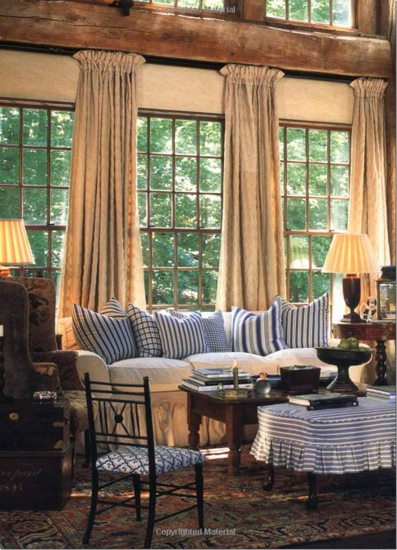 slipcovered ottoman in blue and white stripes mixed in with all the a beautiful country livingroom window drapes