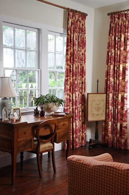 French toile drapes in the bedroom sitting area with a fire screen in the corner
