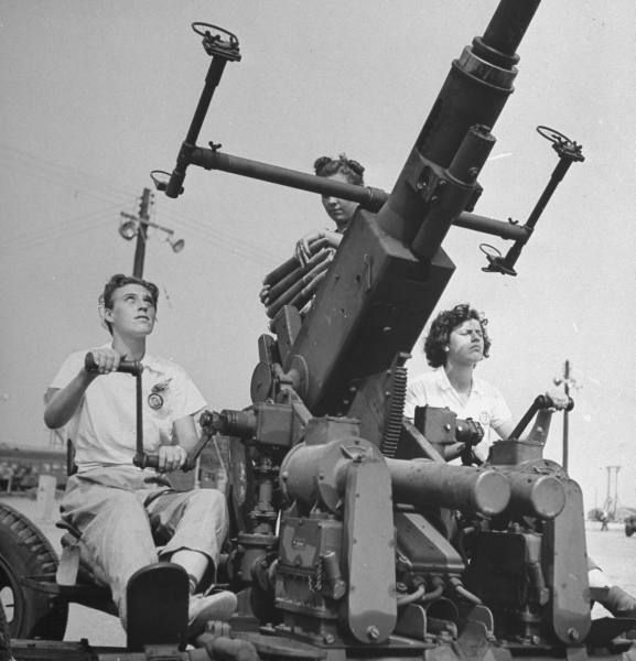 Workers at the Aberdeen Proving Ground in Maryland testing machine guns, 20mm aircraft caynon, sighting on a Bofors AA gun, and a prototype carbine, 1942