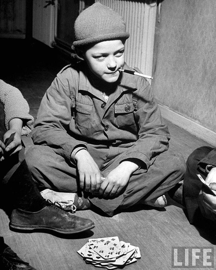Chaval fumando un cigarrillo mientras juega a las cartas en el internado Villa de los Niños, Estocolmo, Suecia (1949)