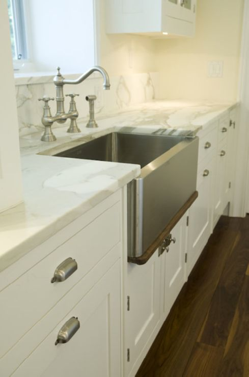 Kitchen with stainless steel apron sink and bridge faucet with carrera marble counters