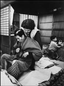 Photo by  Eugene Smith: JAPAN. Minamata. Yahei IKEBA with his wife. They both suffer from the Minamata Disease. Yahei is bedridden and cannot feed himself. 1971.