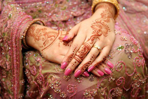 mehndi or henna is applied to the bride's hands and feet in pretty designs