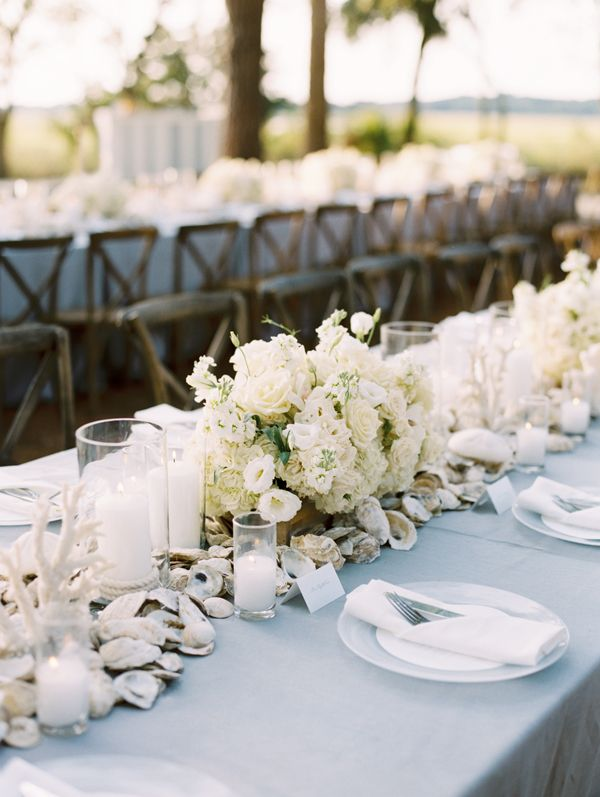 Seashells, white flowers and blue linens for a beach inspired tablescape